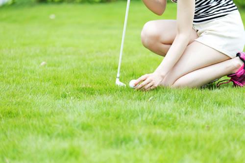 フェアウェイにフォルフボールを置く女性