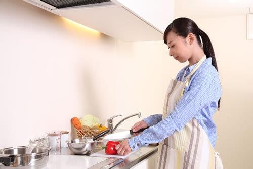 まな板の上でパプリカを包丁で切るポニーテールの女性