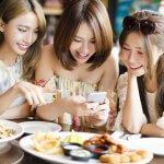 スマホを見ている3人の女子会